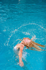 A girl is relaxing in a swimming pool