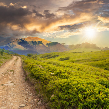 gravel road to high mountains at sunset