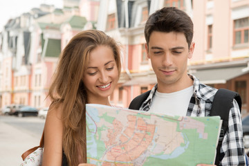 Beautiful couple of tourists holding a map in their hands, conce