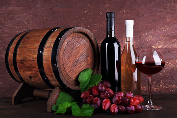 Wine in bottles and in goblet, grapes and wooden barrel