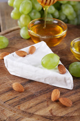 Brie cheese, honey in glass bowl, nuts and grapes