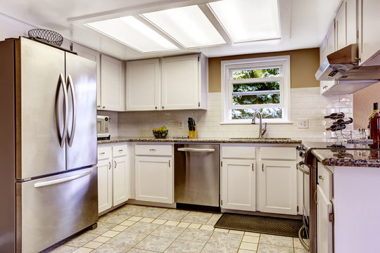 White kitchen room with steel appliances and tile backsplash tri