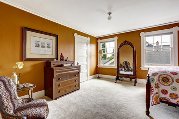 Brown bedroom with antique mirror and cabinet