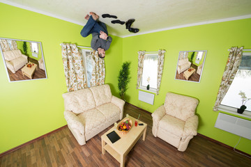 Man in jeans sitting on ceiling without shoes