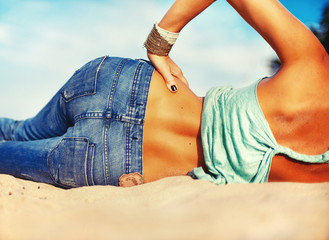 Woman waist and bottom in jeans from backside on the sand.