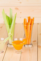 Fresh green celery with carrots in glasses.