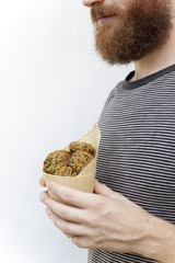 bearded guy holding falafel balls on takeaway paper cornet