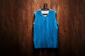 Blue basketball jersey hanging on a wooden wall