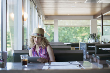 A woman in a hat sitting in a diner, holding a digital tablet, looking at the screen.