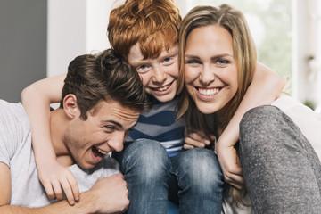 Glückliche junge Familie auf der Couch im Wohnzimmer