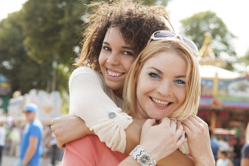 Deutschland, Herne, Zwei junge Frauen auf dem Messegelände tragen einander Huckepack
