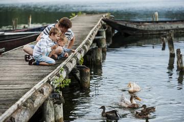 Deutschland, Rheinland-Pfalz, Laacher See, Vater mit Söhnen auf Anlegestelle, Enten füttern