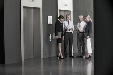 Geschäftsleute sprechen am Aufzug