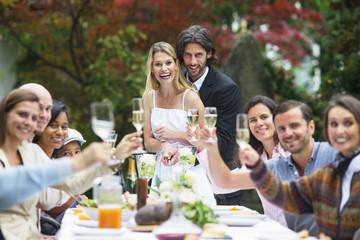 Braut und Bräutigam schneiden Hochzeitstorte auf einer Gartenparty