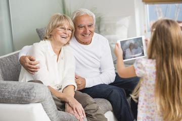 Kleines Mädchen fotografiert ihre Großeltern mit Tablet-PC zu Hause