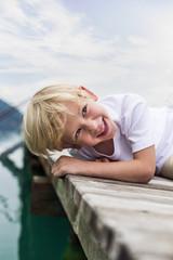Lächelnder kleiner Junge auf einem Steg