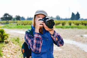cheerful young woman hiking and taking pictures with camera