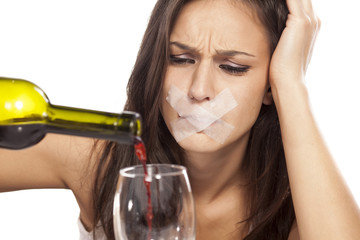girl with sticky tape over her mouth pours wine into a glass