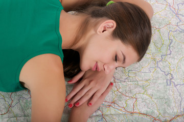 Young woman sleep on the map