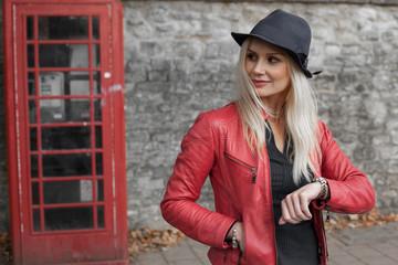 Stylish woman waiting outside a telephone kiosk