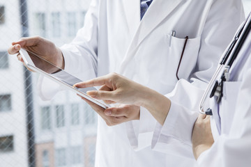 Female physician of two people that use the tablet