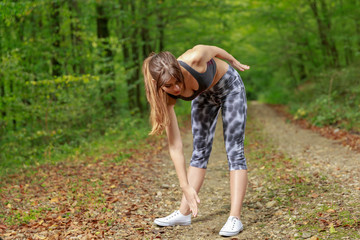 Beautiful young woman doing stretching exercise on road forest