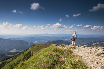 Boy with backpack on mountain hill foot pathe