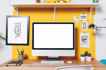 Modern creative workspace on yellow wall.