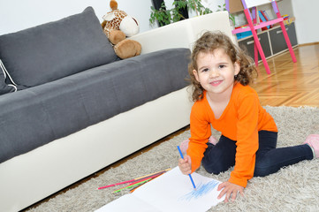 Young girl drawing with coloured pencils