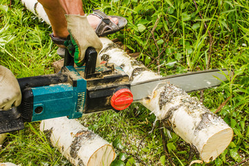 man sawing wood for firewood, using electric chainsaws