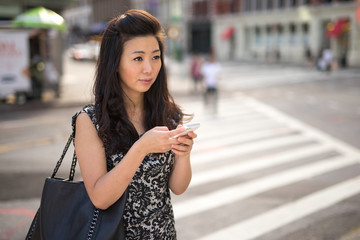 Young Asian Woman texting on cellphone on city street