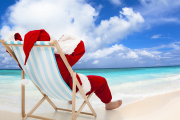 Santa Claus sitting on beach chairs with blue sky and cloud