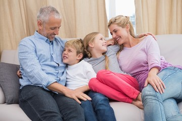 Happy parents with their children on sofa