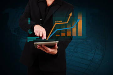 Wall Mural - businessman holding a tablet showing business graph and globe on