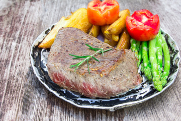 thick juicy portions of grilled fillet steak served with tomatoe