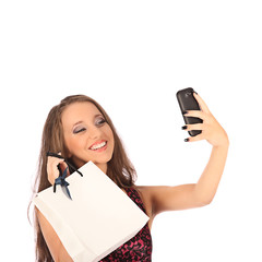 Beautiful girl wiht shopping bags taking selfie with cell phone