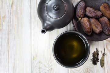 Dried dates on plate with cup of tea on wood table