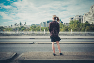 Young woman standing on bridge in city