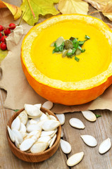 Pumpkin cream soup and seeds on rustic wooden table