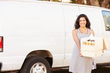 Female Baker Delivering Cakes Standing In Front Of Van