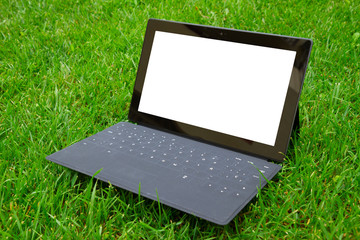 Tablet with keyboard on fresh grass
