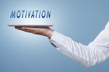 Hand hält Tablet darüber das Wort Motivation