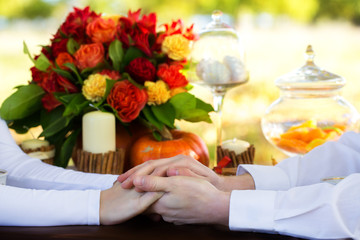 Women's and men's hands with wedding rings at a table decorated
