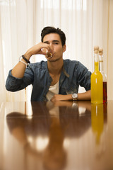 Young man sitting drinking alone at a table