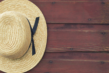 Amish man's straw hat hangs on a red barn door