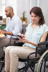 Businesswoman in wheelchair texting on phone