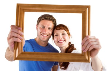 Couple holding frame ahead of them
