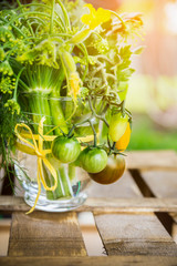 Vegetables in glass vase with yellow bow on old wooden box