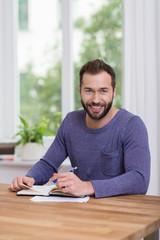 zufriedener mann sitzt am tisch
