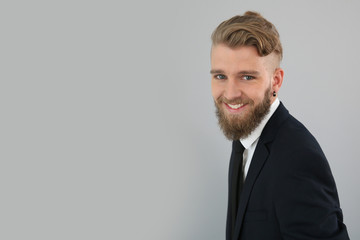 Smiling young businessman on grey background